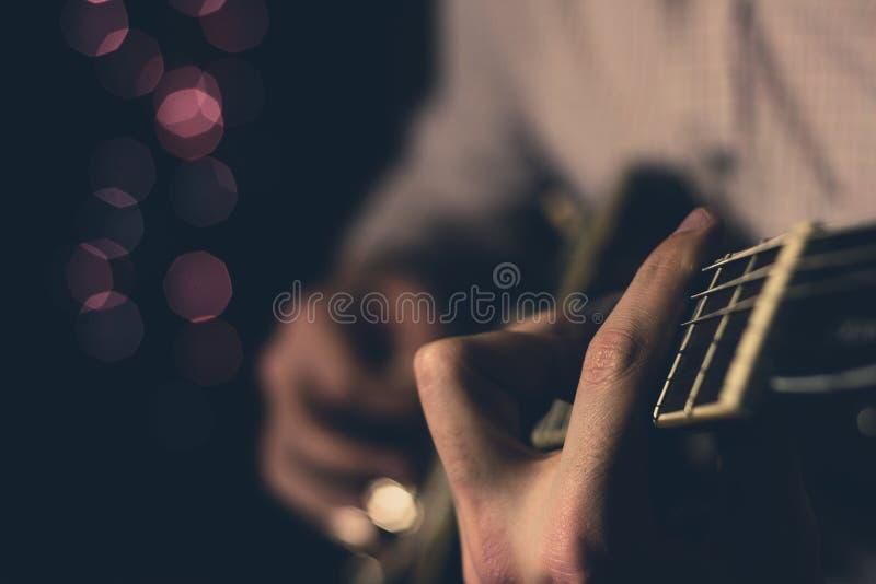 演奏在一把电吉他的一个年轻人蓝色 特写镜头 免版税库存照片
