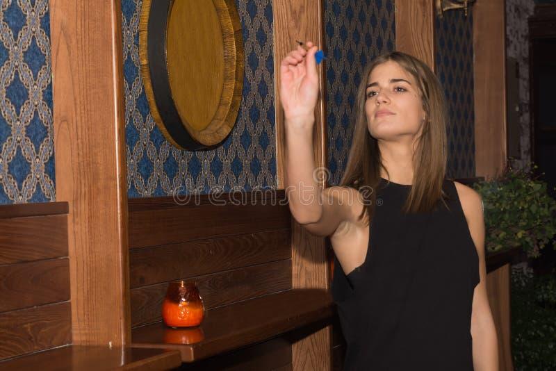 演奏在俱乐部的年轻美丽的妇女箭 库存图片