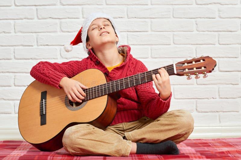 演奏在吉他的男孩音乐,穿戴在一个红色羊毛毛线衣和圣诞老人帽子,坐一条红色方格的毯子,白色砖墙o 免版税库存图片