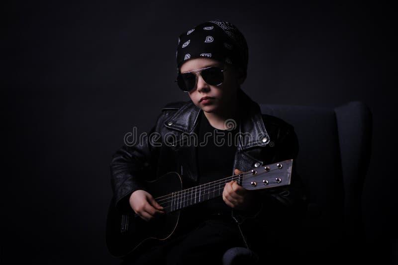 演奏在吉他的皮夹克的一个英俊的男孩摇滚乐, 免版税库存照片