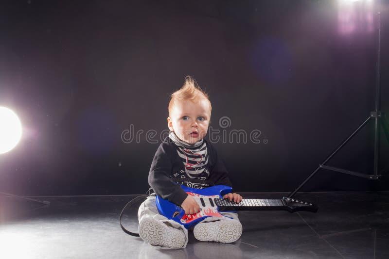 演奏在吉他的小男孩音乐家摇滚乐 免版税图库摄影