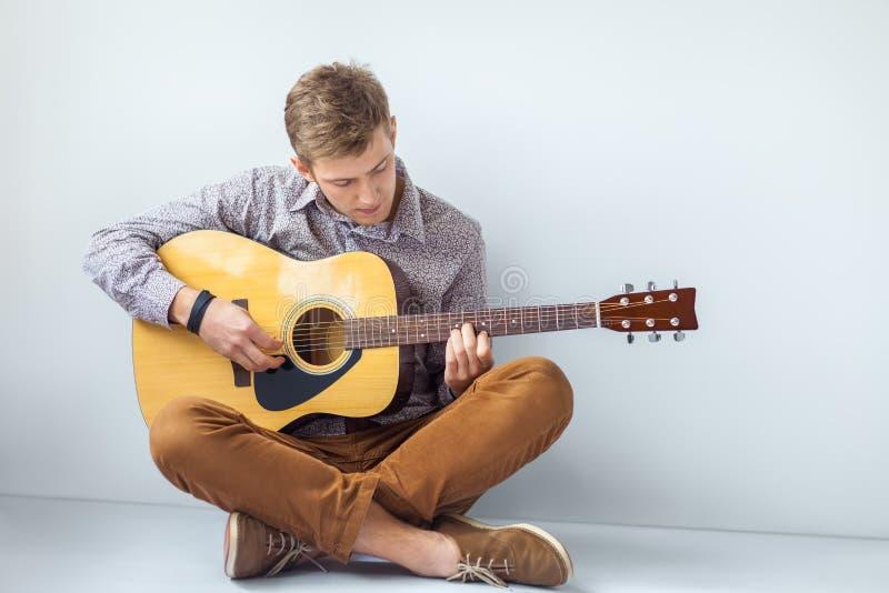 演奏在地板上的英俊的人画象吉他选址 免版税库存照片