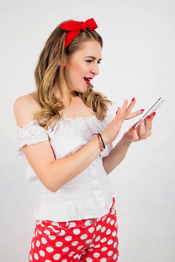 演奏在手机我的样式的美丽,有吸引力的女孩女商人减速火箭的别针灰色背景墙壁 正面人f 免版税库存图片