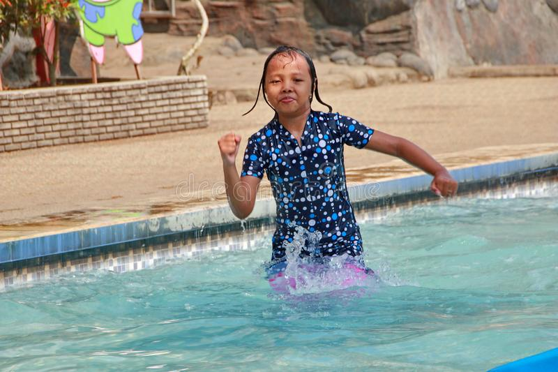 演奏在水池的女孩水 免版税图库摄影