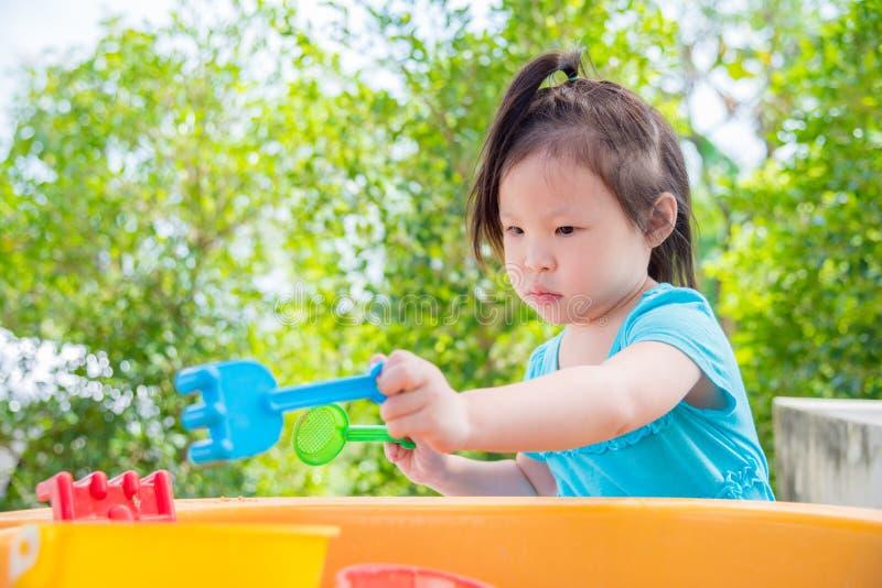 演奏在沙子箱子的女孩沙子 免版税库存照片