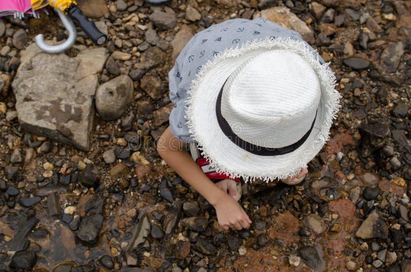 演奏在河的一个小男孩岩石 图库摄影