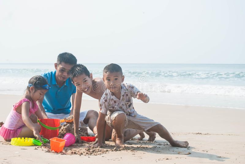 演奏在海滩的父亲和孩子沙子 免版税库存照片