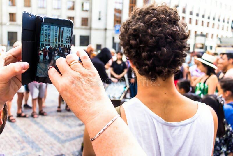 演奏在玻璃的一个黑敞篷的一个年轻人音乐用水布拉格填装了 免版税库存图片