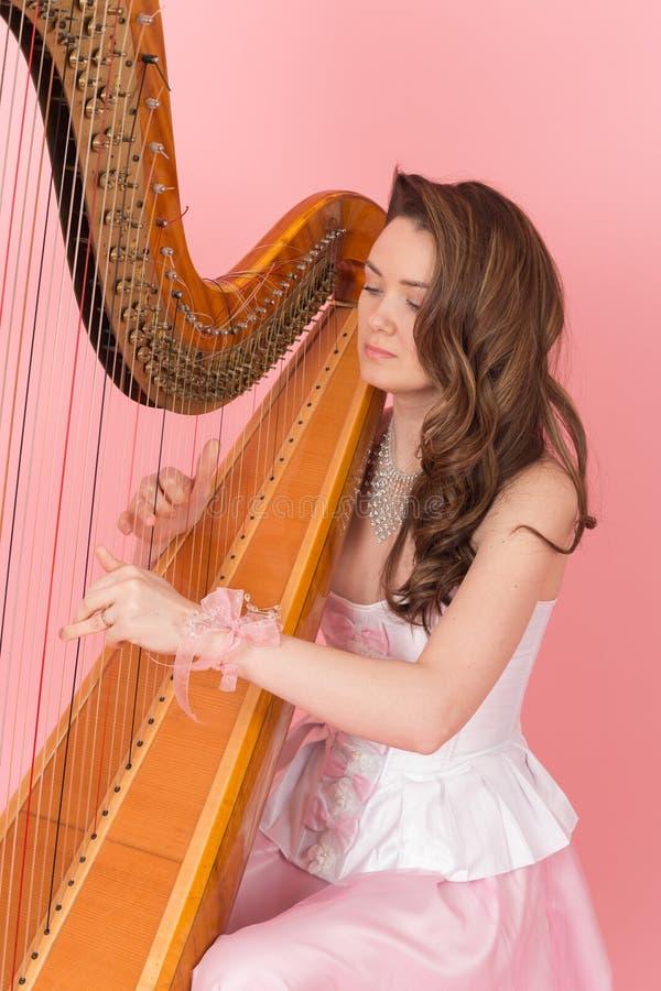 演奏在竖琴的女孩音乐 免版税库存照片