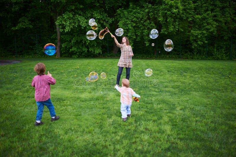 演奏在绿色草坪的妈妈和孩子肥皂泡在公园 免版税图库摄影