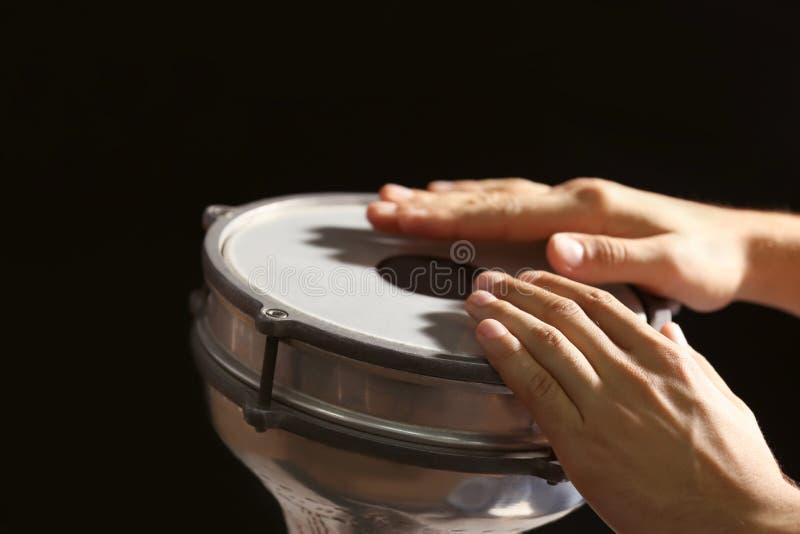演奏在背景的人的手非洲鼓 免版税库存照片