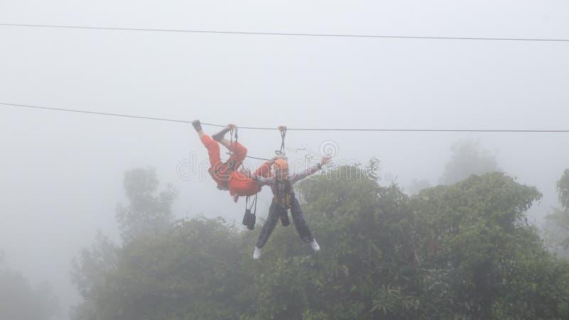 演奏在薄雾的女孩zipline 免版税图库摄影