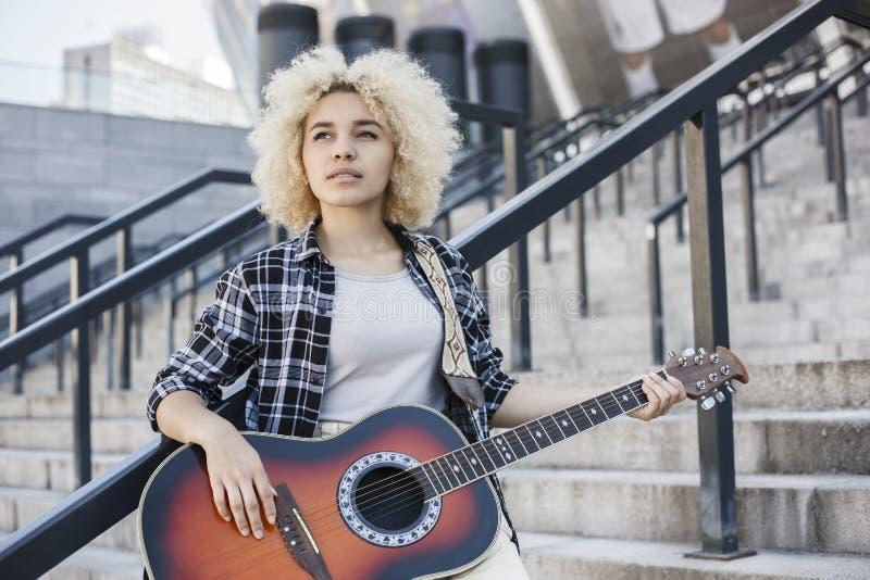 演奏在街道上的可爱的非裔美国人的妇女吉他身分 库存图片