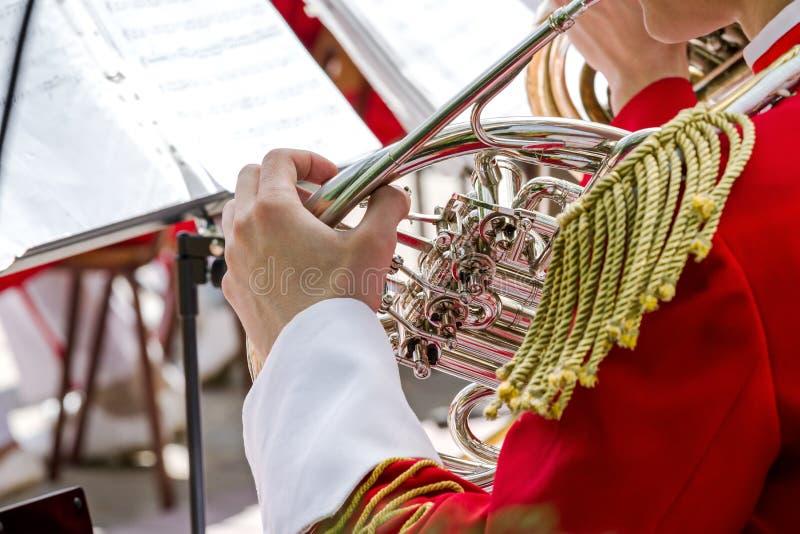 演奏在街道乐队的音乐家法国号 免版税库存照片