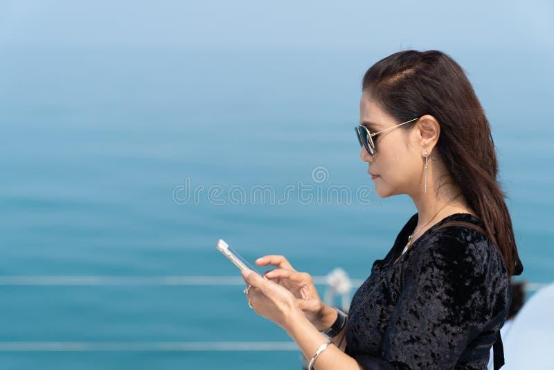 演奏在豪华yacth的富有的女商人巧妙的电话 免版税库存照片