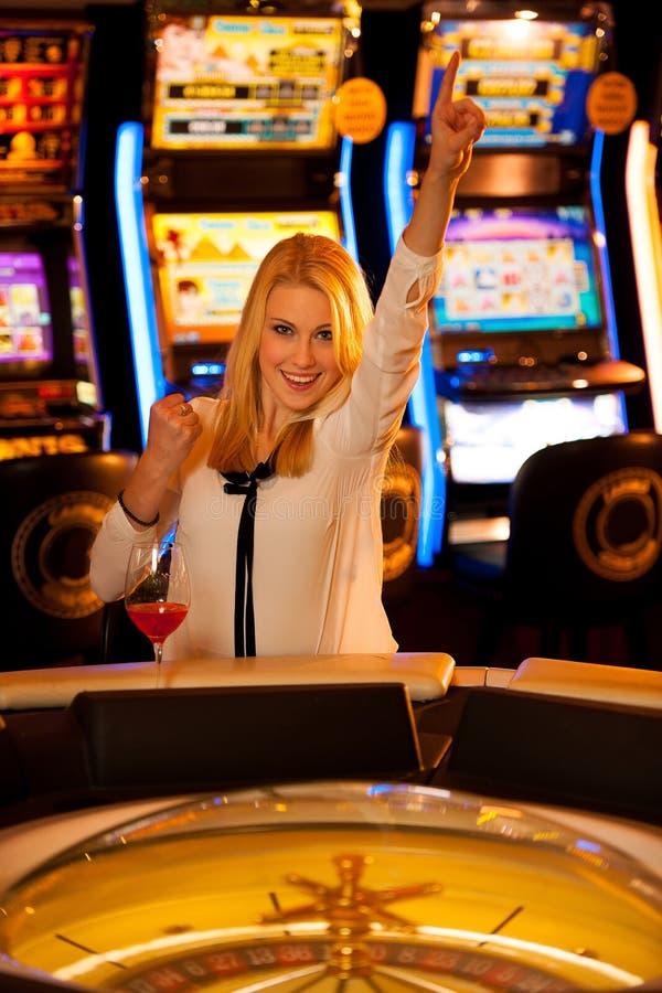 演奏在赌博娱乐场和赢取的年轻白肤金发的妇女轮盘赌 库存图片