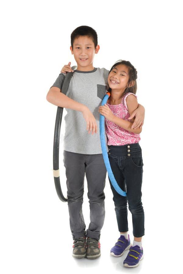 演奏在isol的愉快的矮小的亚裔孩子画象hulahoop 免版税库存照片