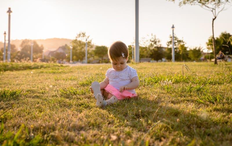 演奏坐草公园的愉快的女婴 免版税库存照片