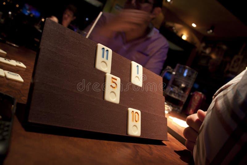演奏垃米纸牌戏的朋友 免版税库存图片