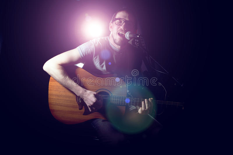 演奏声学吉他和唱歌的音乐家 免版税图库摄影
