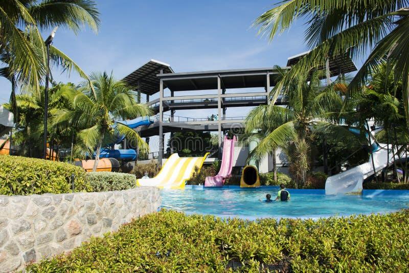 演奏大幻灯片水和游泳在水池的旅客人 免版税库存图片