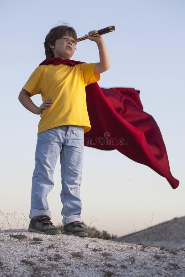 演奏天空背景的男孩超级英雄,一个红色斗篷的少年超级英雄在小山 图库摄影