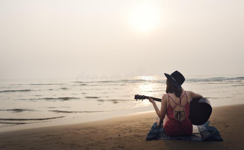 演奏女孩海滩放松歌曲音乐概念的吉他 免版税库存图片