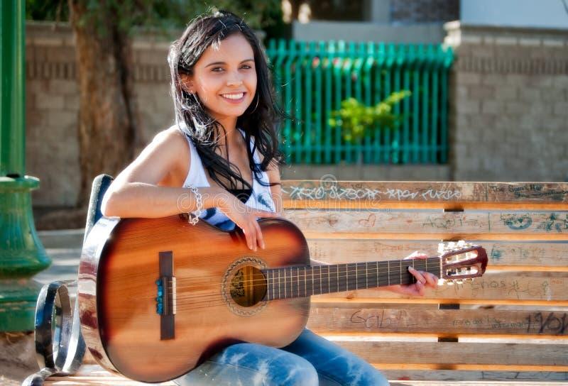 演奏妇女年轻人的吉他公园 免版税库存照片