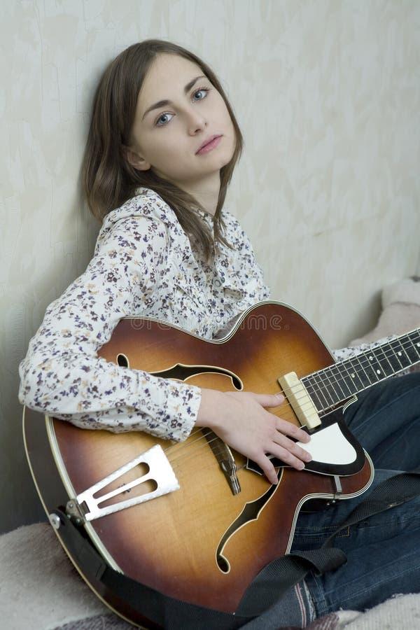 演奏妇女年轻人的有吸引力的吉他 库存图片
