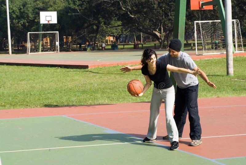 演奏妇女的篮球水平的人 免版税库存图片