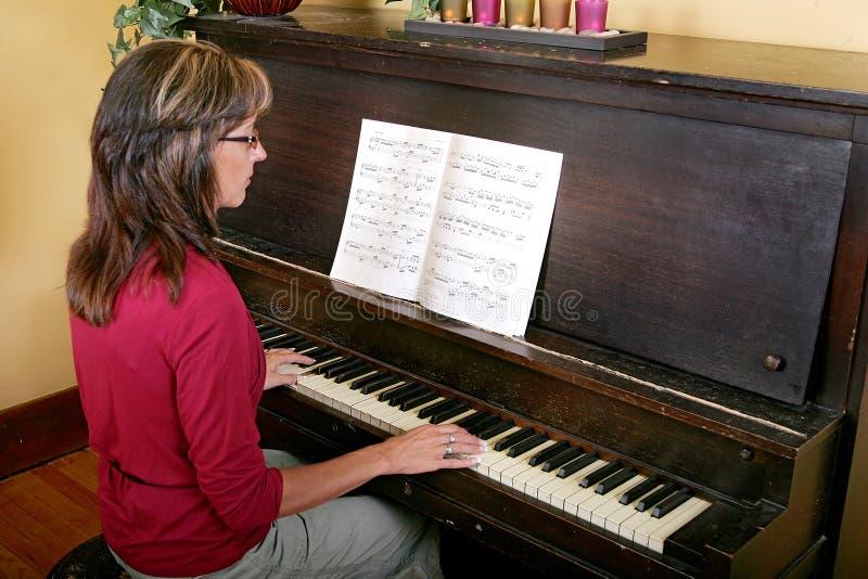 演奏妇女的钢琴 免版税库存图片