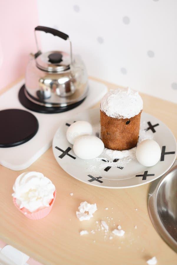演奏孩子的木家具 蛋糕和鸡蛋在桌上和水壶在厨灶 库存图片