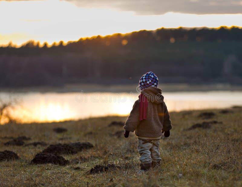 演奏室外近的湖的小男孩 库存图片