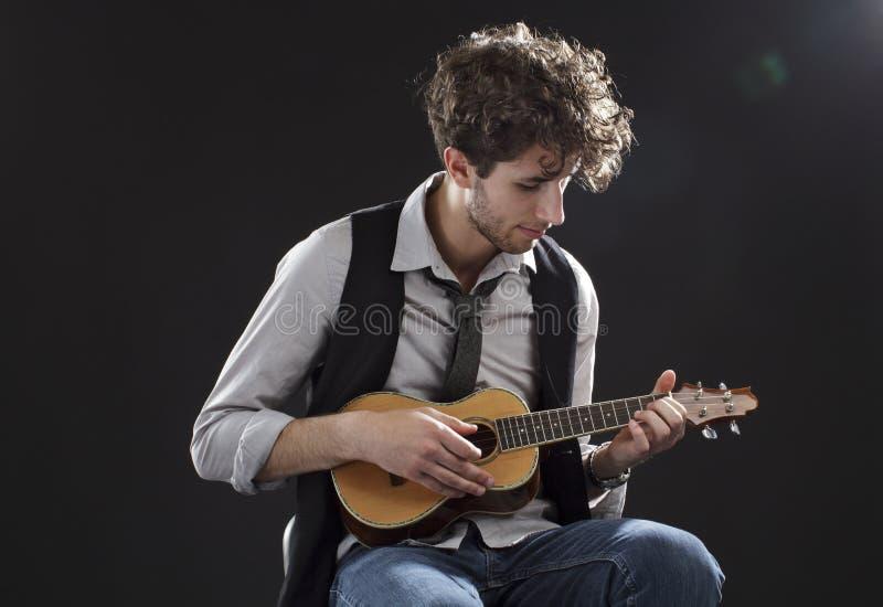 演奏尤克里里琴年轻人的人 免版税库存照片