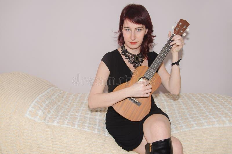 演奏尤克里里琴的美丽的女孩 免版税库存图片