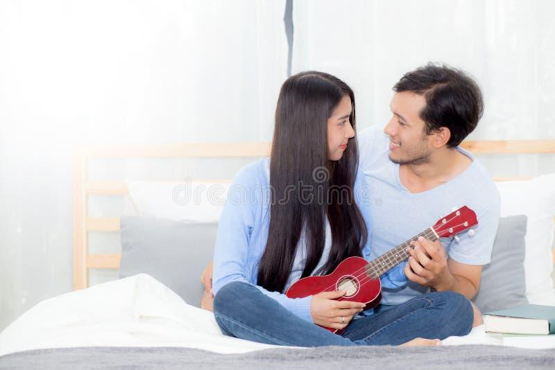 演奏尤克里里琴的年轻亚洲夫妇放松充满幸福 免版税库存图片