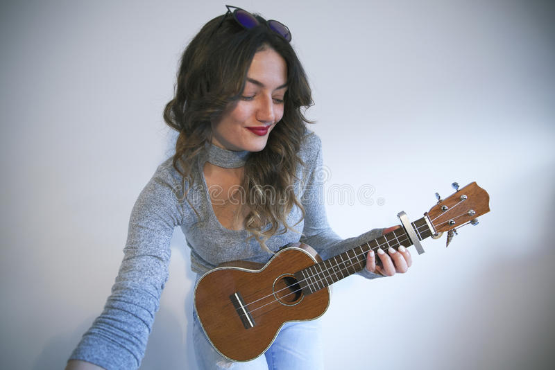 演奏尤克里里琴的年轻美丽的妇女 免版税库存照片