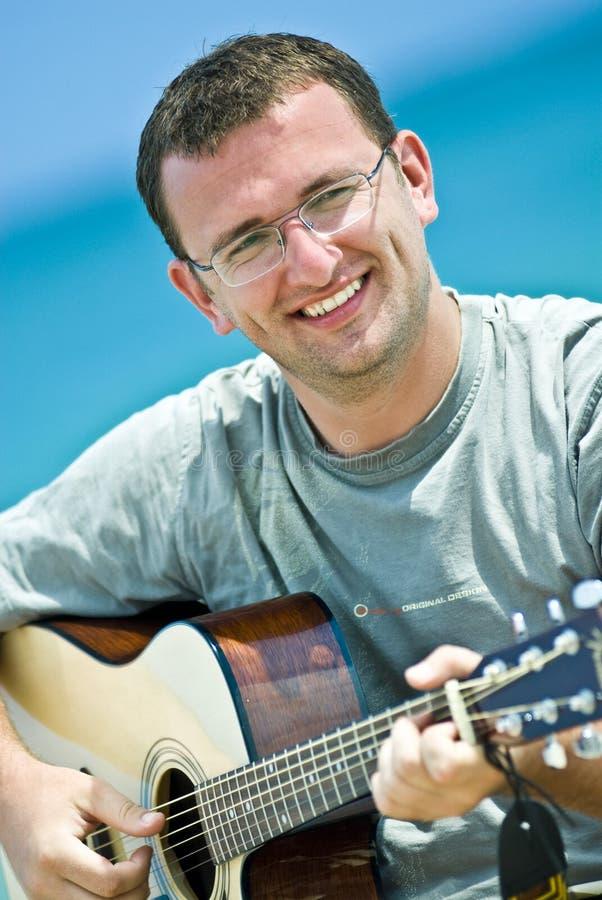 演奏年轻人的吉他人 免版税库存图片