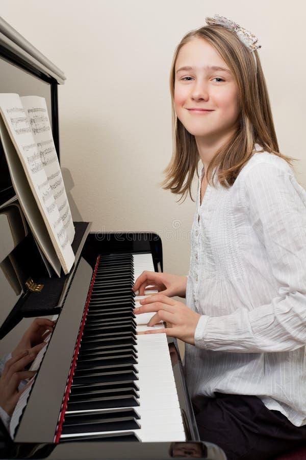 演奏年轻人的女孩愉快的钢琴 免版税库存图片