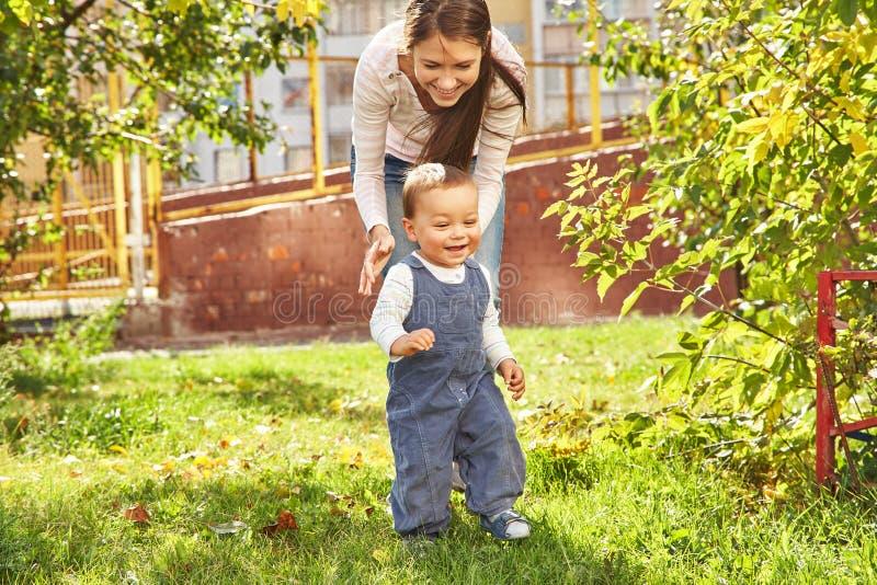演奏年轻人的小母亲 走在公园的妈妈和儿子 图库摄影