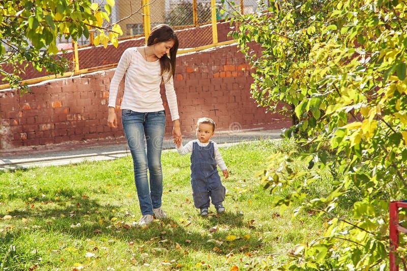 演奏年轻人的小母亲 走在公园的妈妈和儿子 库存照片