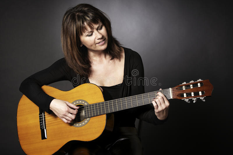 演奏微笑的妇女的吉他 库存照片