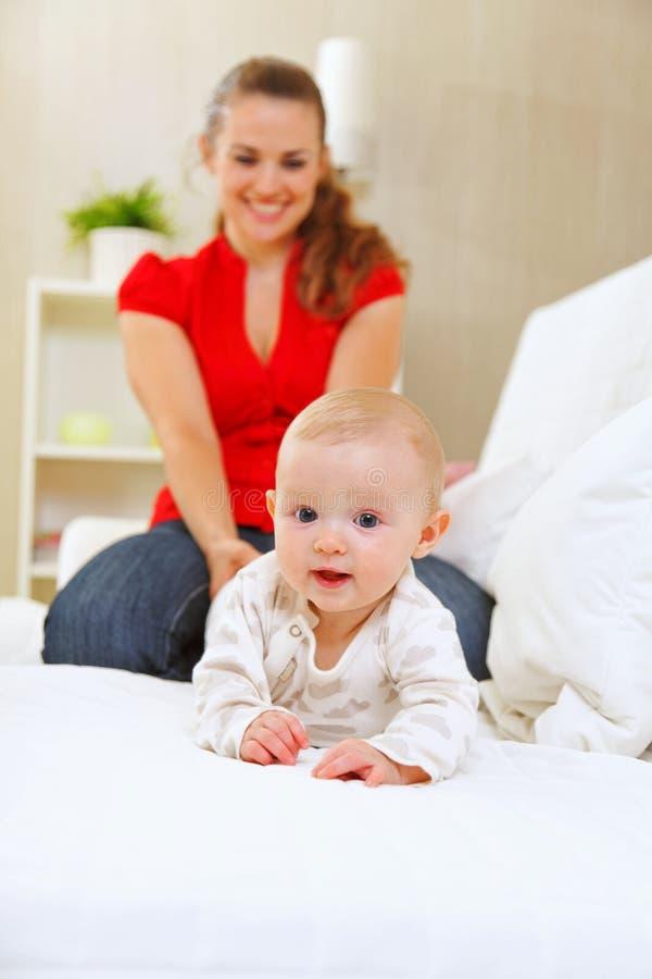 演奏微笑的沙发的可爱的小母亲 图库摄影