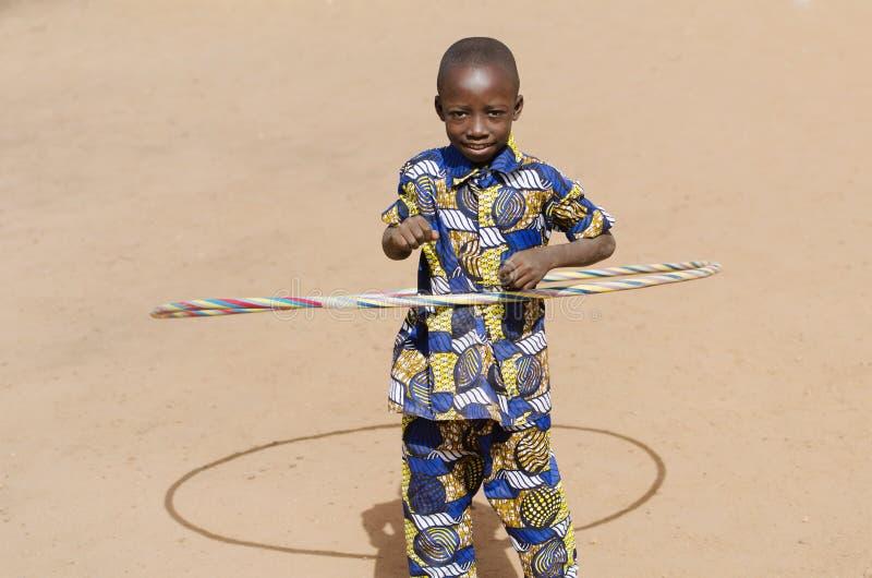 演奏微笑的笑的年轻非洲男孩户外与Hula Ho 免版税库存图片