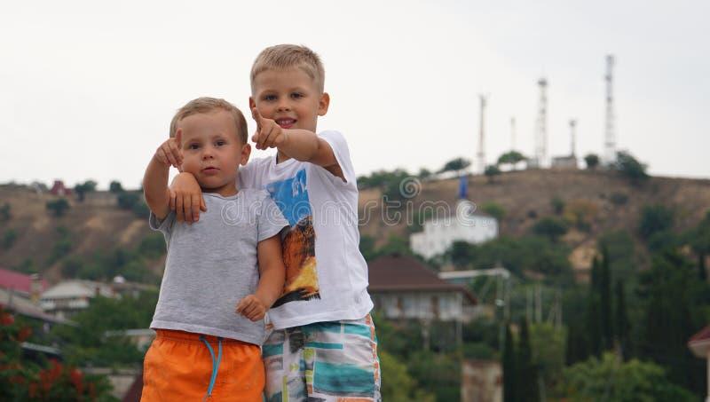 演奏户外一起站立在海的海岸的两个小孩子 免版税库存照片