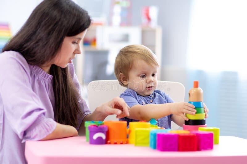演奏教育玩具的逗人喜爱的妇女和孩子男孩在幼儿园或托儿所室 免版税库存图片