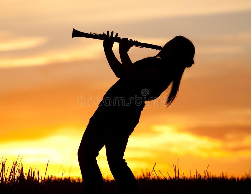 演奏日落的单簧管 免版税库存图片