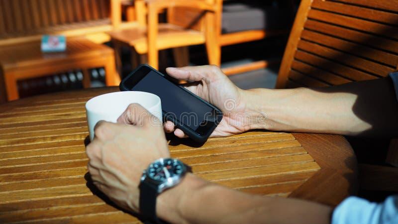 演奏智能手机和喝咖啡的亚洲男性手特写镜头在与早晨阳光的一张室外桌上 所选的重点 免版税库存图片