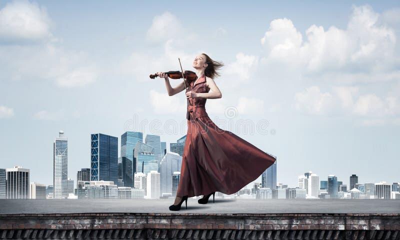 演奏曲调的红色礼服的妇女小提琴手反对多云天空 混合画法 库存照片