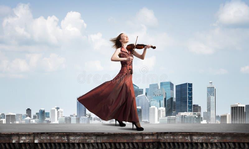 演奏曲调的红色礼服的妇女小提琴手反对多云天空 混合画法 库存图片